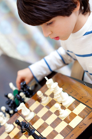 boy learning to play chess photo
