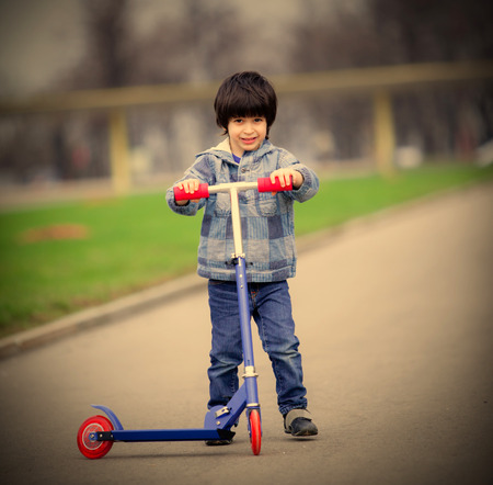 a two wheeled vehicle: a boy with a new scooter on open air Stock Photo