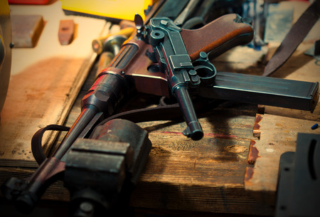 german handgun: Luger pistol and mashinegun MP 38 in gunsmith on old wooden surface. Stock Photo