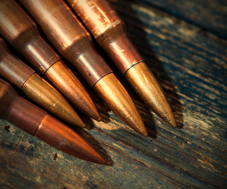 vintage rifle: Still life with several rifle cartridges on vintage wooden surface.