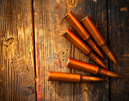 five rifle cartridges on old wooden surfacefive rifle cartridges on vintage wooden surface