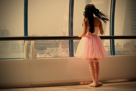sightly: girl doll stands at the window glass gallery back to the camera  Stock Photo