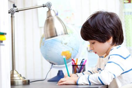 schoolboy doing homework at his desk Stock Photo