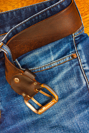 age blue jeans with a leather belt and buckle, close-up Stock Photo