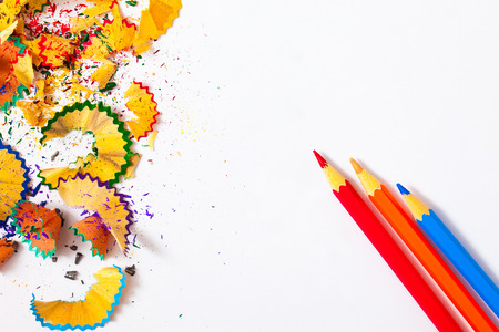 pencil point: three colored pencils and shavings on white background with copy space