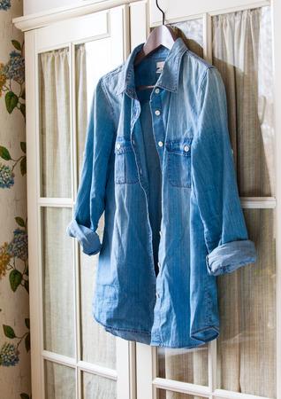 no shirt: denim shirt on a hanger on the door wardrobes Stock Photo
