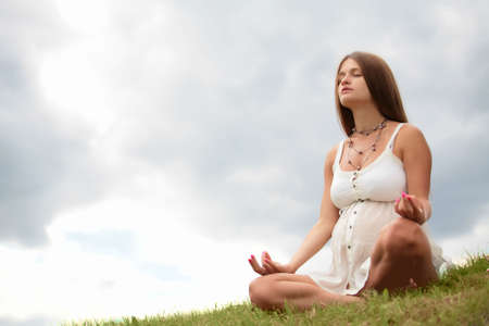 pregnant young woman in light cloth sits on herb and meditating under opened sky