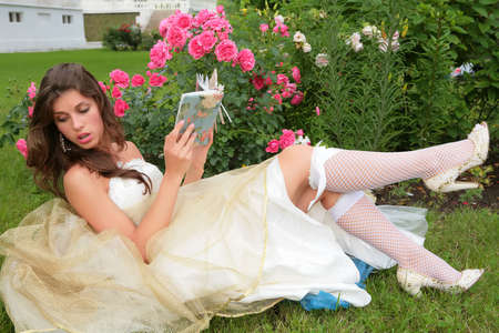girl in image of the princess in white-golden gown reads book under rosebushes