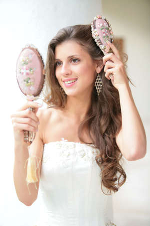 smiling beautiful girl does combs hair old-time comb