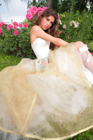 rosebush: portrait of the beautiful girl in luxurious white gown on background of the rosebush