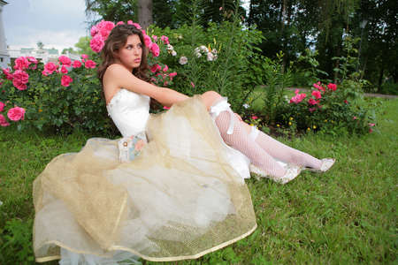 rosebush: portrait of the beautiful girl in luxurious white-golden gown on background of the rosebush