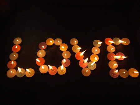 hots: image showing the spelling of the word love with colorful lighted candles on a black background Stock Photo