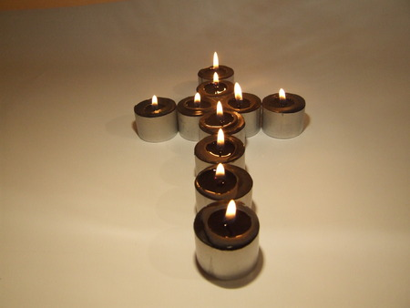 image showing a cross made from small black lighted candles Stock Photo - 1696112