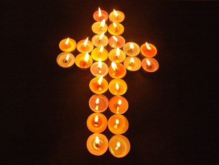 lighted: Cross madle from bright coloured lighted candles