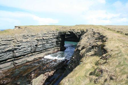 Sea arch along the coast of County Clare Ireland photo
