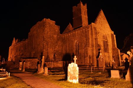 abbey ruins abbey: Ruins of Quin abbey and cemetery at night dating to the 13th century. It is located in county Clare, Ireland Stock Photo