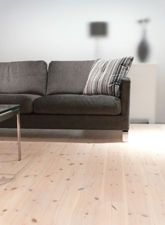 A grey sofa with pillow, a coffee table on a pine wood floor