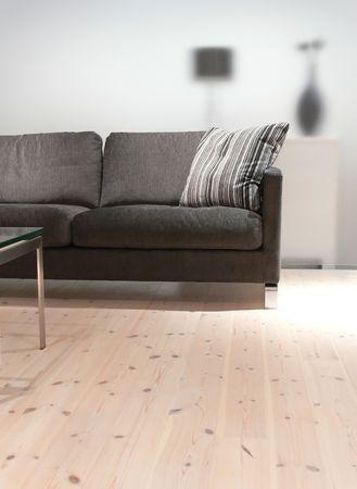 madera pino: Un sof� de color gris con la almohada, una mesa de caf� sobre un suelo de madera de pino  Foto de archivo