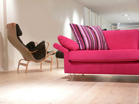A pink sofa with pillows and an armchair on a pine wood floor