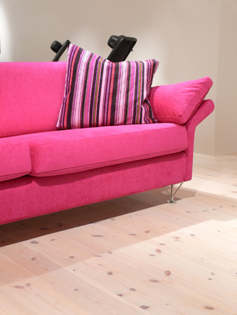 A pink sofa with a striped pillow on a pine wood floor
