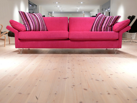 A relaxing pink sofa with pillows on a white pine wood floor Stock Photo