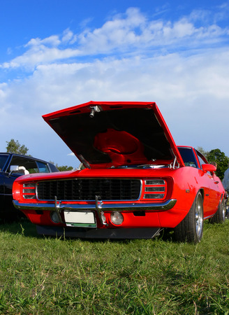 A red american classic car with the hood open