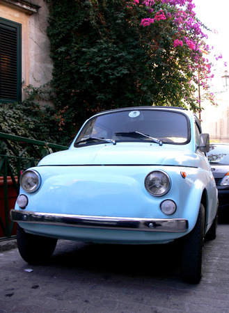 italian car: A tiny italian car parked on one of the small streets of the city of Taormina in Sicaly Stock Photo