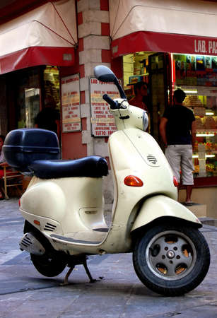 An italian scooter parked outside a bakery and coffee shop in Sicily Italy