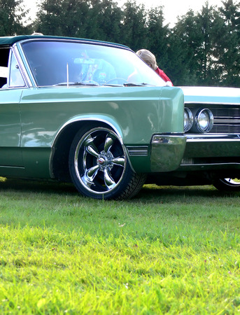 A green classic convertible parked on a green field of grass