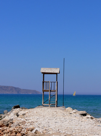 A lonely life guard tower on a stony beach looking out over the open sea - Creet in Greece photo
