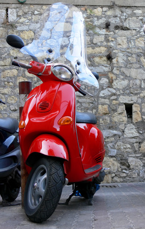 A shiny red italian scooter parked on a narrow street in Italy