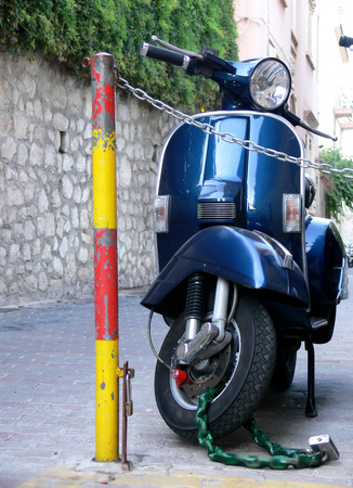 A blue italian scooter parked nad securely loccked on a alley in the city of Taormina Sicily Italy