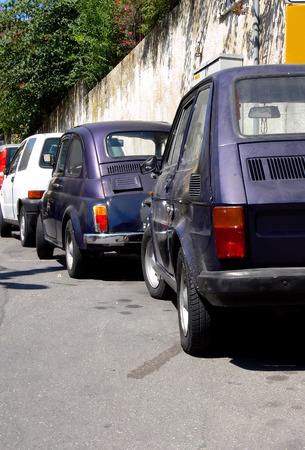 Three generation of tiny italian cars parked on the same street in Sicily Italy photo
