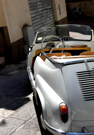 A tiny italian convertible parked on a steep and narrow alley in Sicily Italy