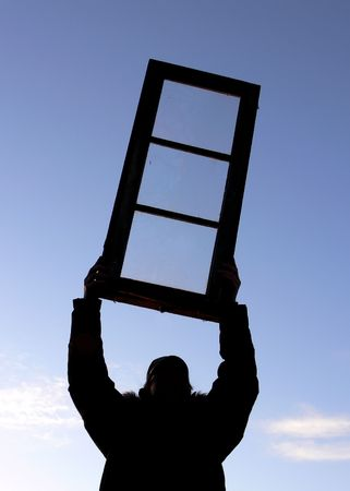 A man holding a window high above his head  Stock Photo