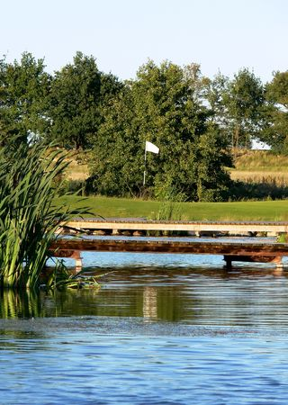 A green area behind two small bridges over a pond on a swedish link golf course