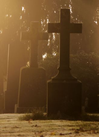 Tombstones with crosses covered in  the morning frost and mist