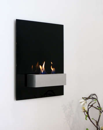 A futuristic designed open fire place hanging on the wall