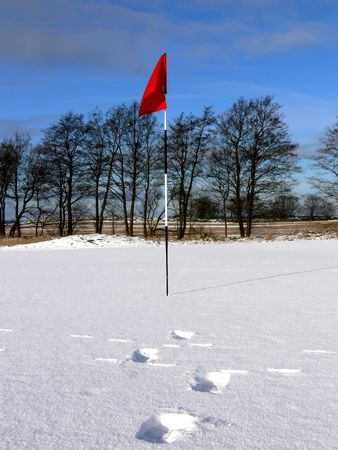 Footprints in the snow leading towards the flag of the 18th hole