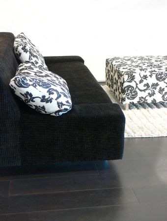 A black sofa with flower pillows and a flower sit puff Stock Photo