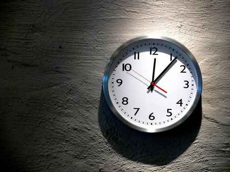 An analog clock hanging on a solid stone wall Stock Photo - 2093978