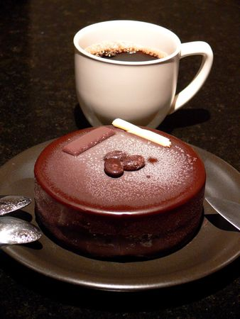 A cup of coffee and icecream cake for dessert