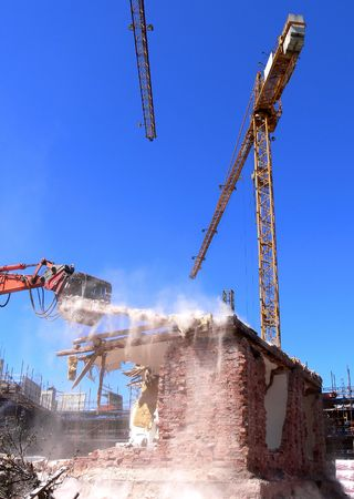 ongoing: Ongoing demolition of a brick  using an excavator, construction cranes in the background raising the new building on the construction site.