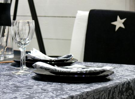 glas: A table set with black plates, napkins and wine glass