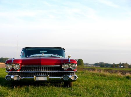 A 1960 metallic red classic american car parked in a green field Stock Photo