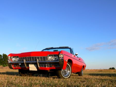 land vehicle: A red convertible frm the 1970 parked in a field Stock Photo