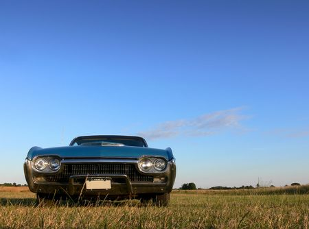 A classic american car parked in a field under a bright blue sky