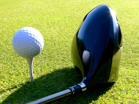 Closeup of a golfball reflecting in a black driver Stock Photo