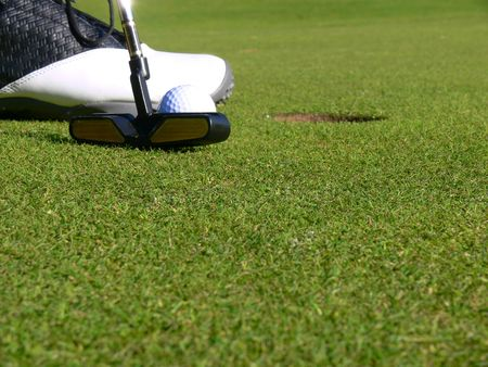 Close-up of a golfer concentrating to sink a short putt