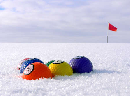 better chances: Golfballs lined up as colorful biljardballs on a snowcovered green area